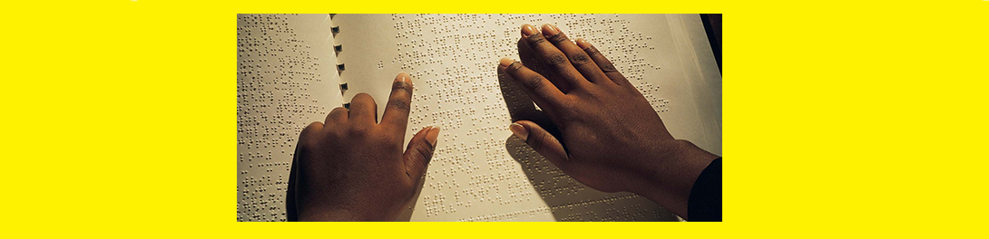 image of a student reading Braille with his hands