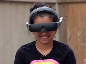 girl wearing eSight glasses looks up, smiling
