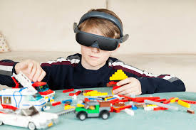 boy wearing eSight glasses while playing with LEGO pieces